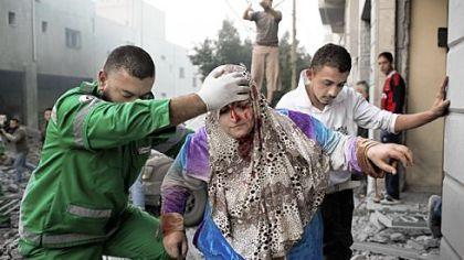 A Palestinian woman is helped by a paramedic Monday from her Gaza City residence, damaged during an Israeli air raid.