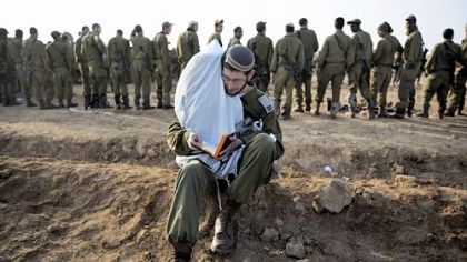An Israeli soldier holds Torah scrolls as prays Monday at an Israeli army deployment area near the Israel-Gaza Strip border in preparation for a potential ground operation in the Palestinian coastal enclave.
