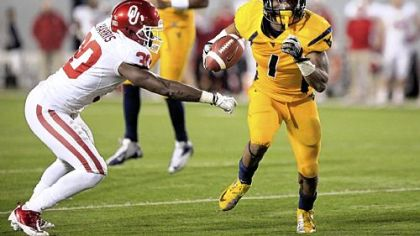 West Virginia wide receiver Tavon Austin (1) slips past Oklahoma&#039;s Javon Harris (30) for a rushing touchdown Saturday in Morgantown, W.Va.