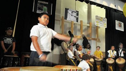 Fourth-grader Roberto Morris plays his drums at the start of the morning assembly at Pittsburgh Dilworth in East Liberty.