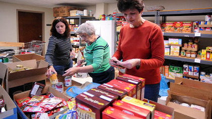 From left, volunteers Karen Corral, Beverly Aufman and Barb Gesmond sort food donations at the North Hills Community Outreach for the annual Thanksgiving food distribution.
