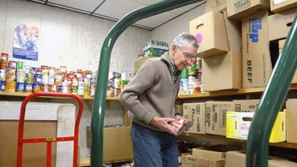Elmer Brown, 92, of McDonald packs food Thursday at the McDonald Area Food Bank. Borough council recently recognized him for his 30 years of service to the food bank.