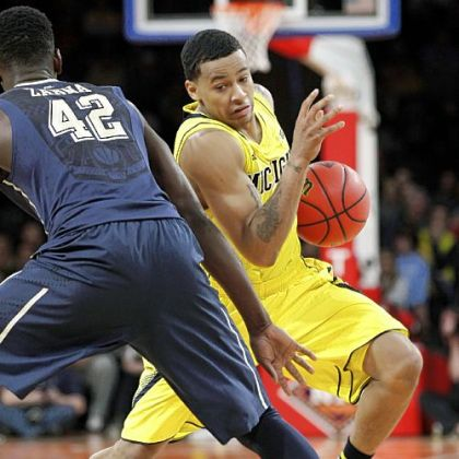 Michigan&#039;s Trey Burke, right, attempts to drive around Pitt&#039;s Talib Zanna in the semifinals of the NIT Season Tip-Off Wednesday night at Madison Square Garden.