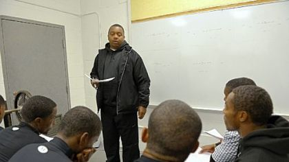 Defensive coach Wayne Wade, 40, goes over strategy with the Bears in the team's weight room in November. Wade, who is from Clairton, was the team's quarterback in 1989 when the Bears won the WPIAL Class A championship.