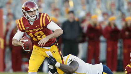 Iowa State quarterback Sam Richardson, left, scrambles as he is pulled down by West Virginia defensive lineman Shaq Rowell, right, during the first half of an NCAA college football game Friday, in Ames, Iowa.