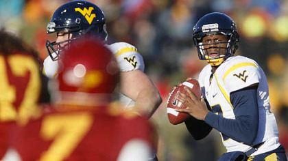 West Virginia quarterback Geno Smith, right, drops back to pass during the first half of an NCAA college football game against Iowa State, Friday, in Ames, Iowa.