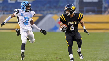 North Allegheny's Elijah Zeise carries as as he's defended by Woodland Hills' Trevon Mathis Friday in the WPIAL class AAAA championships at Heinz Field.