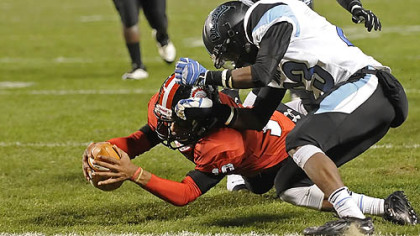 Aliquippa&#039;s Malik Shegog dives into the end zone for a touchdown as he&#039;s defended by Washington&#039;s Darius Spinks Friday in the WPIAL class AA championships at Heinz Field.