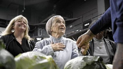 Mary Jane Ehrler, 89, of Brighton Heights, center, greets the Steelers' Maurkice Pouncey during a Thanksgiving turkey give-away Wednesday, presented by the Max Starks Hometown Team and the Greater Pittsburgh Community Food Bank at Stage AE on the North Shore. Patty Van Dillen, left, is the special events coordinator for the food bank.