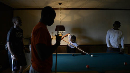 Members of the Clairton Bears shoot pool at Hot Towels And Sharp Razors barber shop on St. Clair Avenue.
