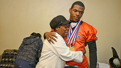 Ann Marie Ford hugs her son Robbie Boatright at their Clairton home. Ford said she is proud of her son and his Bears teammates. They put us on the map, she says.