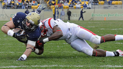 Pitt&#039;s Mark Giubilato dives for yardage as he&#039;s defended by Rutgers&#039; Jamal Merrell in the second quarter this afternoon at Heinz Field.
