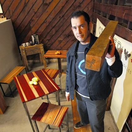"Sal Tamayo, 35, owner of Against the Grain, shoulders a timber of ""rescued"" wood once used as dunnage by a steel shipping company. He salvages the castoff exotic hardwood from the Port of Los Angeles and makes tables, chairs and benches."