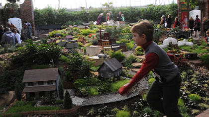 Jonathan Peters, 6, of McMurray races along the edge of the garden railroad in the South Conservatory on the opening day of Phipps' Winter Flower Show.