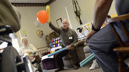 Alan Romatowski takes part in an exercise with other patients at Concordia Adult Day Services, using foam sticks to bat away balloons.