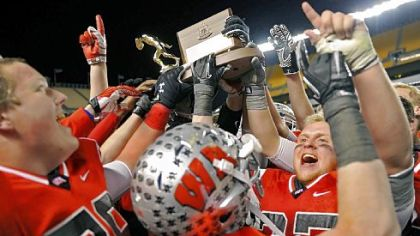 Joyous West Allegheny players hoist the WPIAL championship trophy after the Indians defeated West Mifflin, 34-8, last Friday at Heinz Field.