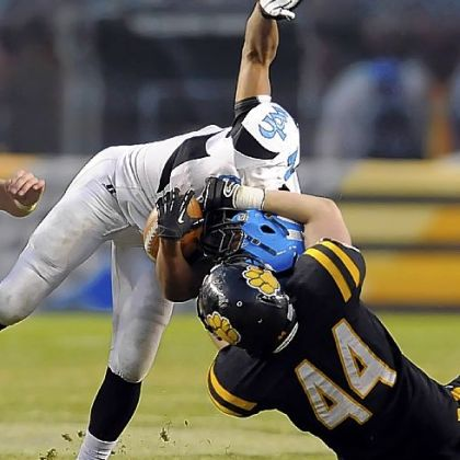 Woodland Hills' Dequan White is pulled down by North Allegheny's Kevin Edwards during WPIAL championship game at Heinz Field.