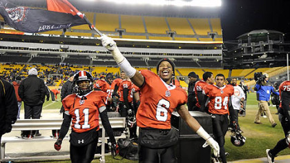 Aliquippa's Dravon Henry waves his school's flag after defeating Washington Friday in the WPIAL class AA championships at Heinz Field.