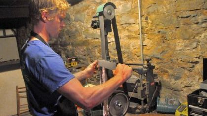 John Heidelmeier grinds an edge on a knife blank in Bar Marco's basement workshop.