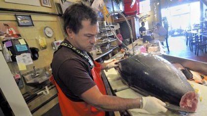 Henry Dewey, at Penn Fish Co, dismantles a large tuna in the shop.