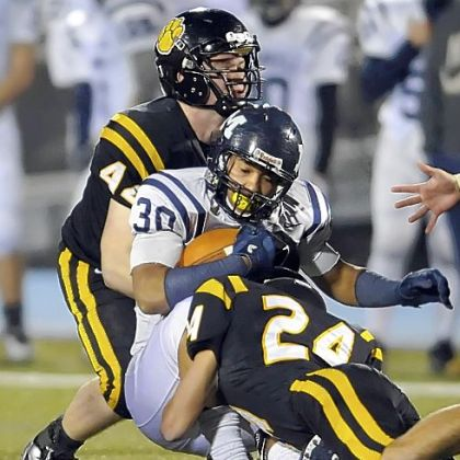 North Allegheny's Kevin Edwards and Ben Schweiger take down McDowell's James Conner Friday night.