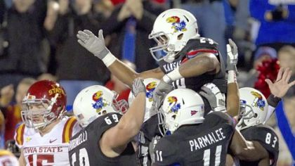 Kansas running back James Sims (29) celebrates with teammates after a big play as Iowa State defensive lineman Ben Durbin (15) walks off the field during the first half in Lawrence, Kan., Saturday, Nov. 17, 2012.