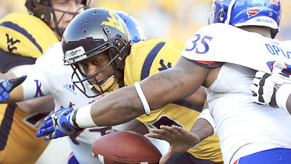 West Virginia quarterback Geno Smith is sacked by Kansas' Toben Opurum (35) and John Williams (71) during the second quarter. West Virginia will play former Big East rival Syracuse in the New Era Pinstripe Bowl Dec. 29 according to Post-Gazette source.