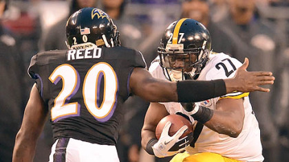 The Steelers' Jonathan Dwyer picks up yardage against the Ravens' Ed Reed in the first half.