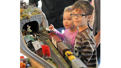 Annaleigh Bouchard, 3, of White Oak watches the model railroad trains with her brother Chucky, 5, at the Carnegie Science Center on the North Shore on Saturday.
