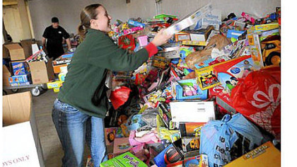 Colleen Balistrieri of Brentwood works with her husband, Nino, background, to unload boxes of toys for the Marine Corps' Toys for Tots program at Guardian Storage in the Strip District.