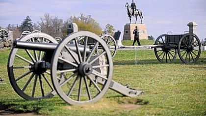 A visitor walks along the Union Army artillery pieces on Cemetery Ridge.