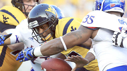 West Virginia quarterback Geno Smith is sacked by Kansas' Toben Opurum (35) and John Williams (71) during the second quarter.