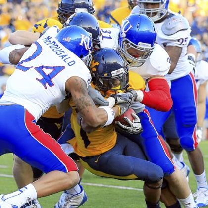 Kansas' Bradley McDougald (24) and Ben Heeney (31) tackle Tavon Austin in the first quarter.