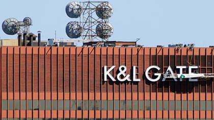 Workers fasten the new K&L Gates sign on the building formerly known as One Oliver Plaza in 2009.