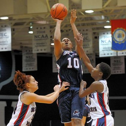 Duquesne junior Wumi Agunbiade gets a shot off Sunday as Robert Morris' Ashley Ravelli, left, and Jasmine Tate defend.
