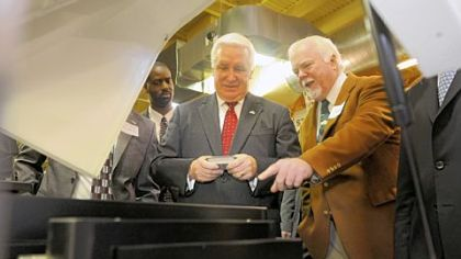 Kent Rockwell, chairman and CEO of ExOne, right, shows Gov. Tom Corbett parts manufactured by ExOne in North Huntingdon during a visit to Acutronic.