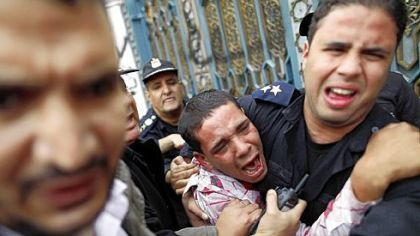 Egyptian police protect an opposition demonstrator after a scuffle with members of the Muslim Brotherhood and supporters of Egypt&#039;s Islamist President Mohammed Morsi during clashes outside the presidential palace in Cairo on Wednesday.