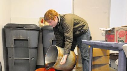 Travis Mecum, an Energy Corps Fellow of GTECH,  collects waste oil from the kitchen of Phipps Conservatory in Oakland.