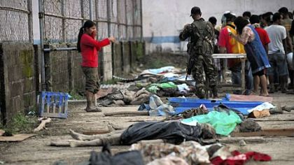 Residents try to identify the bodies of relatives in New Bataan, Compostela Valley province Wednesday, a day after Typhoon Bopha hit the province.