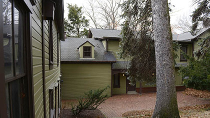 The back of the house features a red brick pation and mature trees.
