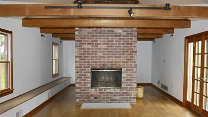 The media room, created by previous owners from part of a barn, has a beamed ceiling and double-sided wood-burning fireplace.