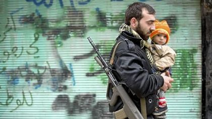 A rebel fighter carries his son after Friday prayers in al-Fardos, a neighborhood in Aleppo, Syria.