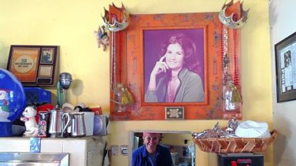 Older Carman looks out from her little kitchen under the gaze of younger Carman.
