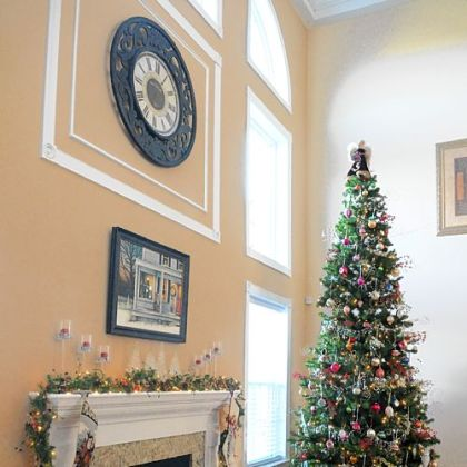 The living room in the home of Carol and Gerald Johnson is highlighted by a tree with some ornaments more than 40 years old, a Christmas painting above the fireplace and a reindeer mat in front of it.