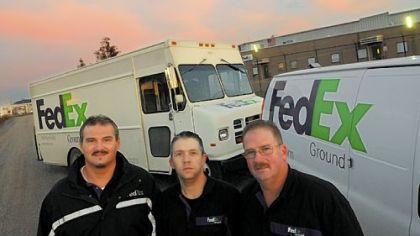 Bill Floyd, Tom Dunlap and Paul Bullock in front of their delivery trucks and the Neville Island FedEx warehouse.