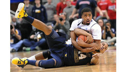 Duquesne&#039;s Sean Johnson fights for possession with West Virginia&#039;s Gary Browne in the second half.