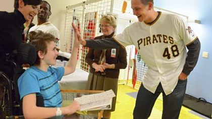 Pitcher Jared Hughes gives a high-five to Garrett Morgan, 15, of Erie, Tuesday while Stacy Eber, left, an occupational therapist at the Children's Institute of Pittsburgh, and Hughes' teammate Andrew McCutchen look on.