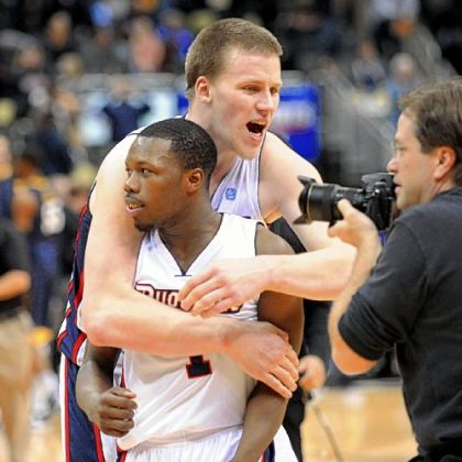 Duquesne's Martins Abele, rear, hugs teammate Derrick Colter Tuesday after the Dukes rallied to beat West Virginia, 60-56, at Consol Energy Center.
