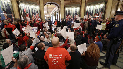 Protesters sit in the rotunda of the State Capitol in Lansing, Mich., Tuesday, Dec. 11, 2012. The crowd is protesting right-to-work legislation passed last week.