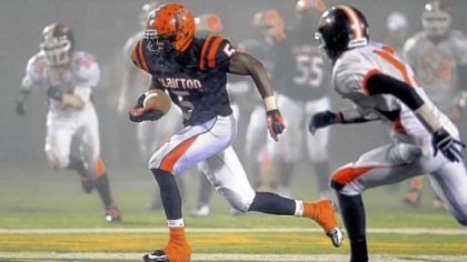 Clairton&#039;s Terrish Webb breaks through the gloom and mist at Deer Lakes High School and away from the Port Allegany defenseto gain yardage.